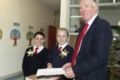 Lt. Col Gerry O'Gorman (Rtd) is greeted by David Rogan and Claudia Murray -two school ambassadors from 6h class - as he arrives at St. Anne's School, Ardclough for the Presentation of the National Flag and 1916 Proclamation to the school.