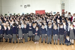 Pupils and tachers stand to sing The National Anthem